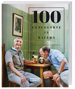 Zwei Männer sitzen am Tisch und trinken Bier.