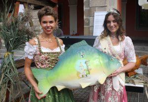 Zwei Frauen halten einen Karpfen aus Plastik hoch