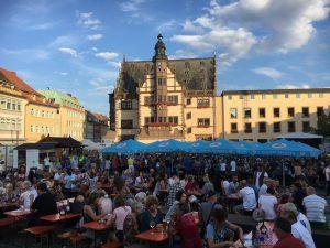 Weinfest am Marktplatz, viele Besucher sitzen gemütlich an Bänken